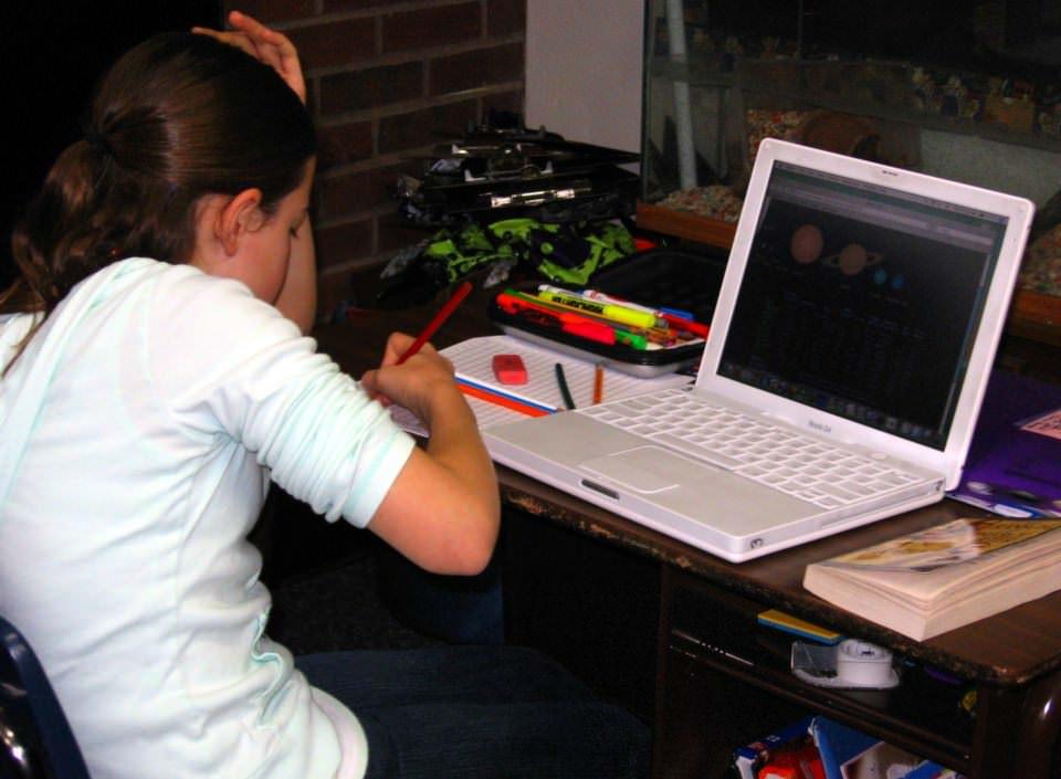 Devojčica radi domaći ispred računara